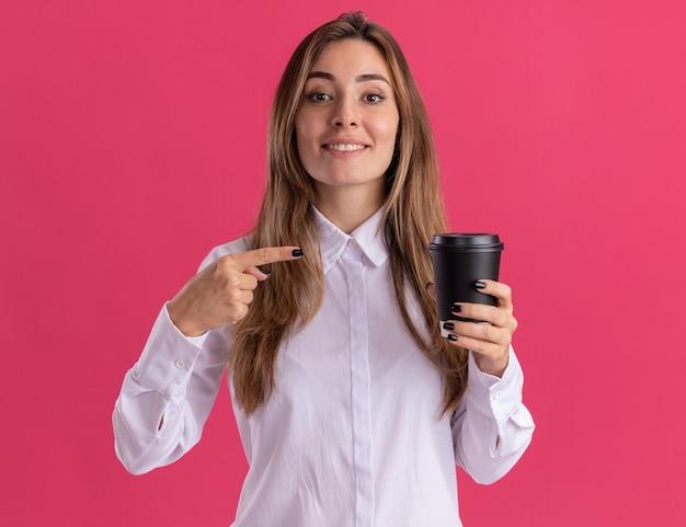 Jovem e bonita caucasiana sorridente segura e aponta para o copo de papel rosa