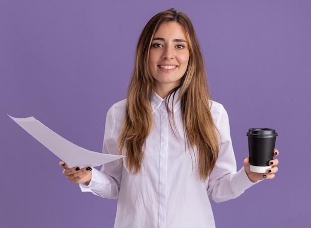 Jovem e bonita caucasiana sorridente segurando folhas de papel e um copo para viagem