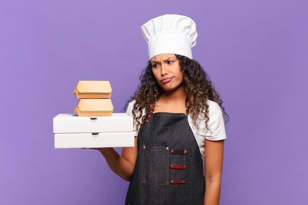 Jovem e bonita churrasqueira segurando caixas de comida para viagem