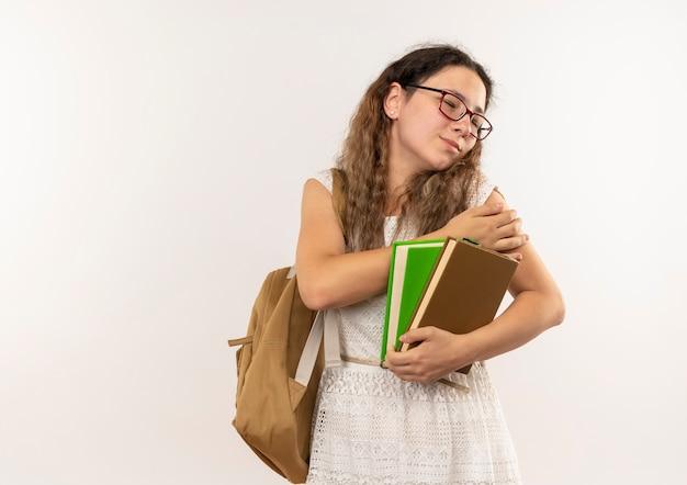 Jovem e bonita colegial dolorida usando óculos e uma bolsa nas costas segurando livros, colocando a mão no braço com os olhos fechados, isolado no branco com espaço de cópia