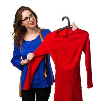 Jovem e bonita costureira com fita métrica e um vestido vermelho