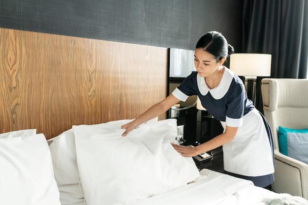 Jovem e bonita empregada colocando travesseiro em roupa de cama branca limpa enquanto troca de cama em um dos quartos do hotel durante a preparação para novos hóspedes