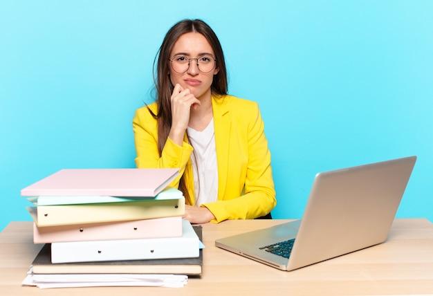 Jovem e bonita empresária parecendo séria, confusa, incerta e pensativa, duvidando de opções ou escolhas