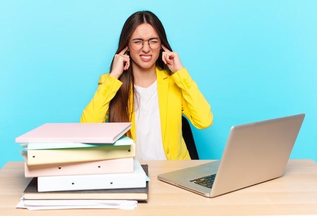 Jovem e bonita empresária parecendo zangada, estressada e irritada, cobrindo ambos os ouvidos com um barulho, som ou música alta ensurdecedores