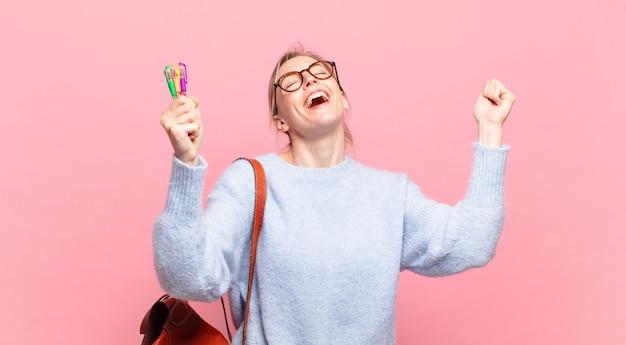 Jovem e bonita estudante celebrando uma vitória bem-sucedida