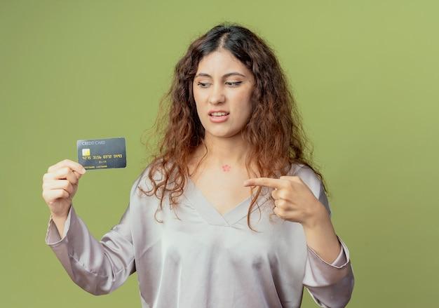 Jovem e bonita funcionária de escritório impressionada segurando e apontando para o cartão de crédito