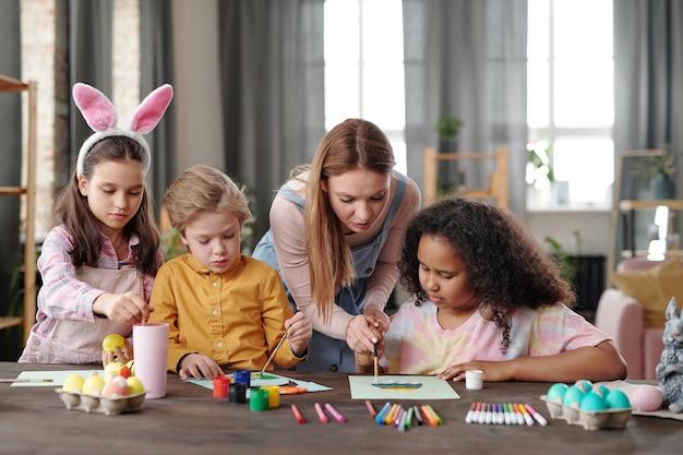 Jovem e bonita loira curvando-se sobre a mesa com um grupo de crianças enquanto os ajuda a pintar um quadro de ovo de páscoa antes do feriado