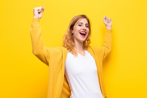 Jovem e bonita loira gritando triunfantemente, parecendo vencedora animada, feliz e surpresa, comemorando contra a parede amarela