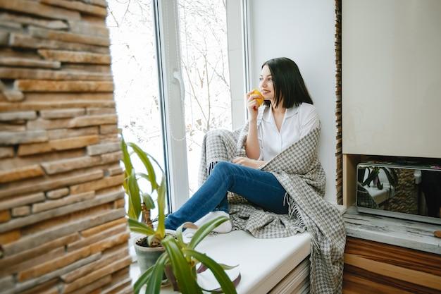 Jovem e bonita morena sentada perto da janela na cozinha com limão