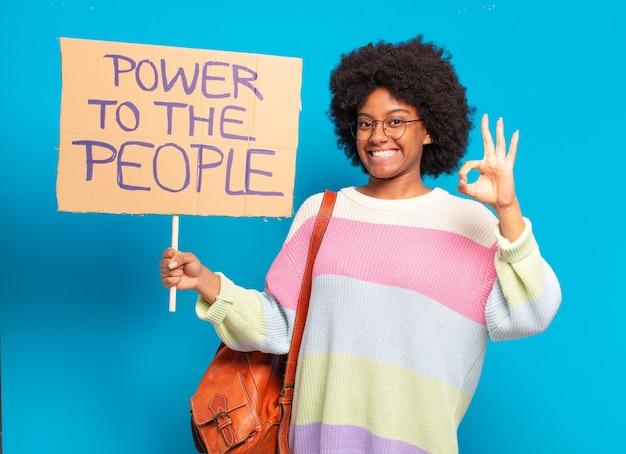 Jovem e bonita mulher afro protestando com um estandarte de poder para o povo