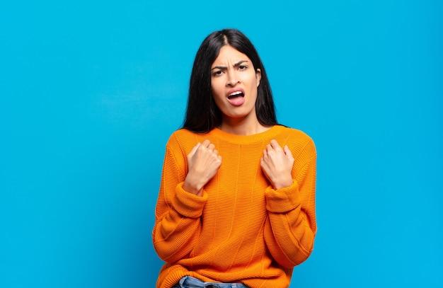 Jovem e bonita mulher hispânica gritando agressivamente com olhar irritado, frustrado e irritado e punhos cerrados, sentindo-se furiosa