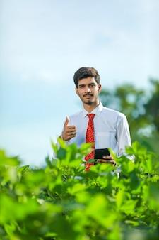 Jovem e bonito agrônomo segura um tablet touch pad no campo de algodão e examina as plantações