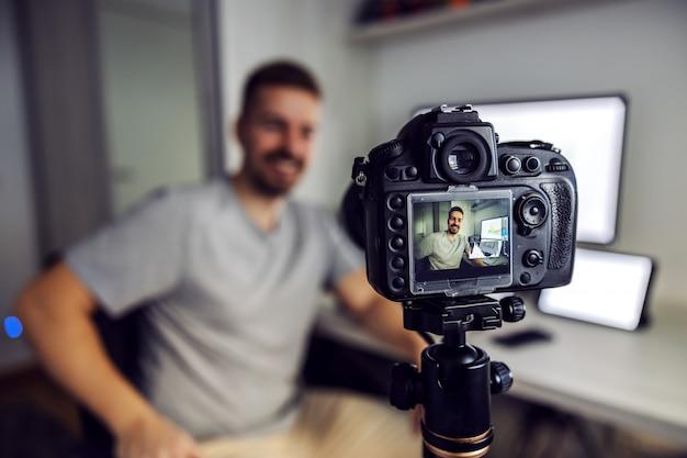 Jovem e bonito blogueiro barbudo filmando-se no escritório em casa. ele está falando sobre como ganhar mais dinheiro no mercado de ações.