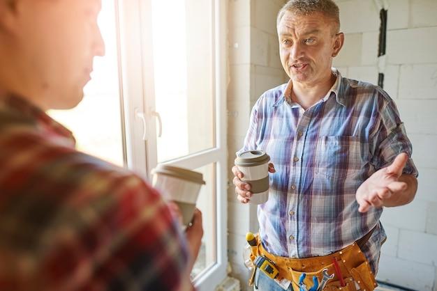 Jovem e bonito carpinteiro trabalhando com um homem experiente