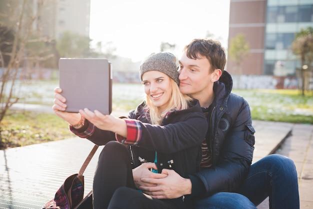 Jovem e bonito casal caucasiano sentado em uma calçada
