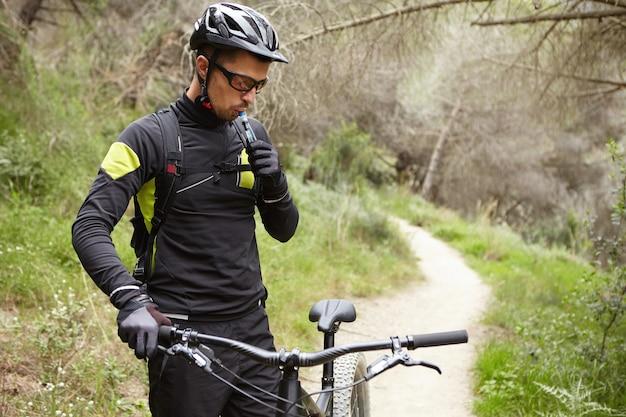 Jovem e bonito ciclista de montanha europeu com roupas esportivas e equipamento de proteção em pé