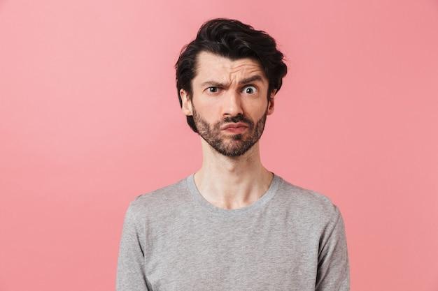 Jovem e bonito confuso homem barbudo moreno usando suéter em pé rosa