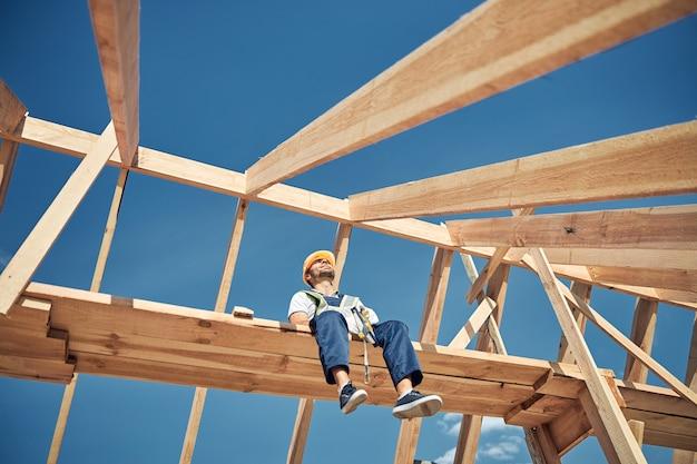 Jovem e bonito construtor sentado na viga e levantando a cabeça enquanto faz uma pausa