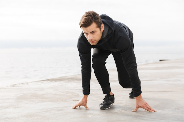 Jovem e bonito desportista confiante a fazer exercício na praia, pronto para começar a correr, a posar