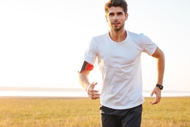 Jovem e bonito desportista correndo ao ar livre e ouvindo música com fones de ouvido