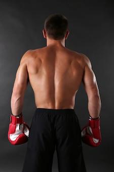Jovem e bonito desportista musculoso com luvas de boxe na superfície escura