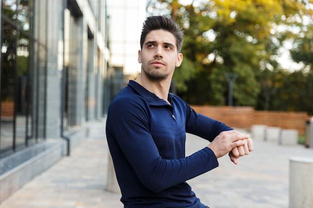 Jovem e bonito desportista parado ao ar livre, verificando o tempo