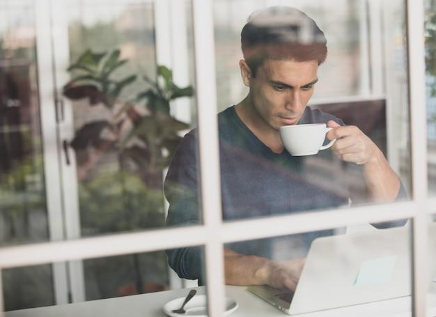 Jovem e bonito empresário caucasiano vestindo um pano casual, sentado alegremente em casa, bebendo café e usando o computador laptop laptop. ideia para trabalhar em casa. atire através da parede de vidro do espelho.