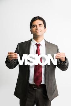 Jovem e bonito empresário indiano asiático segurando uma bandeira ou placa em que palavras diferentes são escritas por um recorte de papel na cor branca, isolado sobre um fundo branco