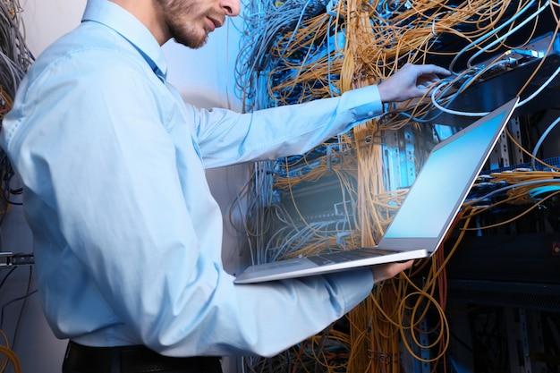 Jovem e bonito engenheiro com laptop na sala do servidor