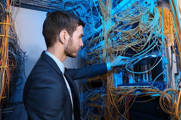 Jovem e bonito engenheiro trabalhando na sala do servidor