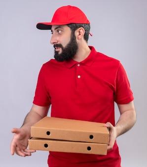 Jovem e bonito entregador caucasiano vestindo uniforme vermelho e boné segurando caixas de pizza e olhando para o lado isolado no fundo branco