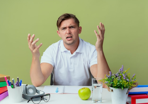 Jovem e bonito estudante confuso sentado na mesa com as ferramentas da escola, espalhando as mãos isoladas no verde oliva