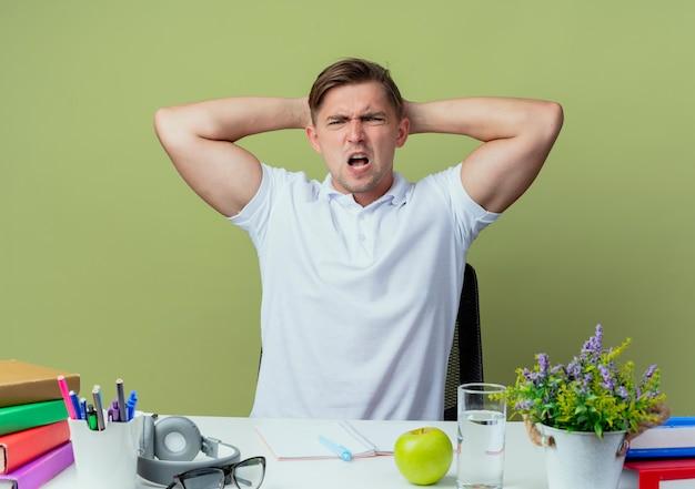 Jovem e bonito estudante do sexo masculino com raiva sentado na mesa com as ferramentas da escola, colocando a mão atrás da cabeça, isolado no verde oliva