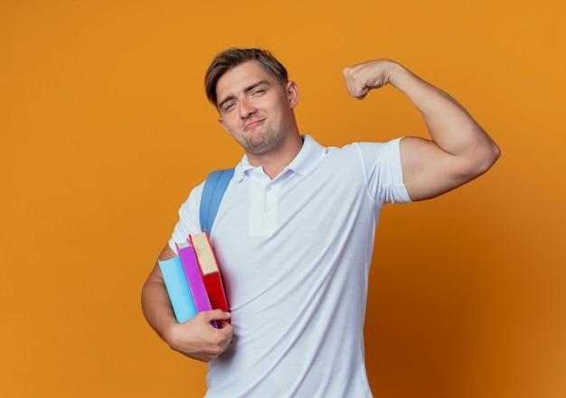 Jovem e bonito estudante do sexo masculino com uma bolsa nas costas segurando livros