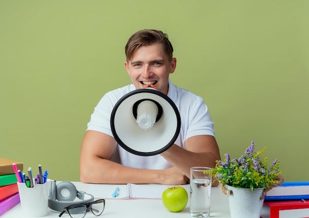 Jovem e bonito estudante do sexo masculino sorridente, sentado na mesa com as ferramentas da escola, fala no alto-falante isolado em verde oliva