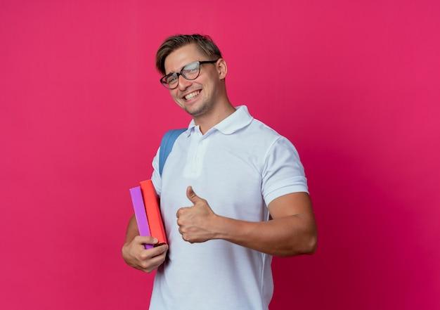 Jovem e bonito estudante do sexo masculino sorridente usando bolsa e óculos segurando livros