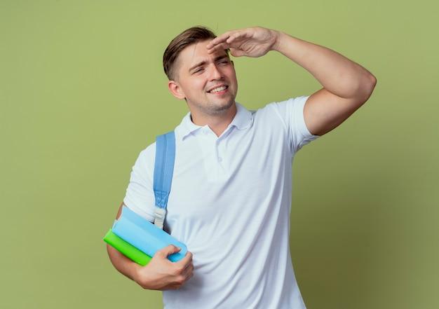Jovem e bonito estudante do sexo masculino sorridente, vestindo uma bolsa traseira, olhando para a distância com a mão e segurando um livro isolado em verde oliva