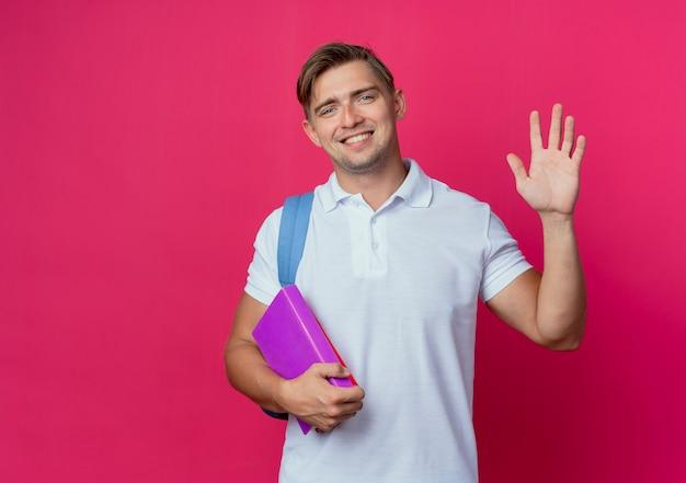 Jovem e bonito estudante sorridente usando uma bolsa com livros e mostrando um gesto de olá isolado na parede rosa