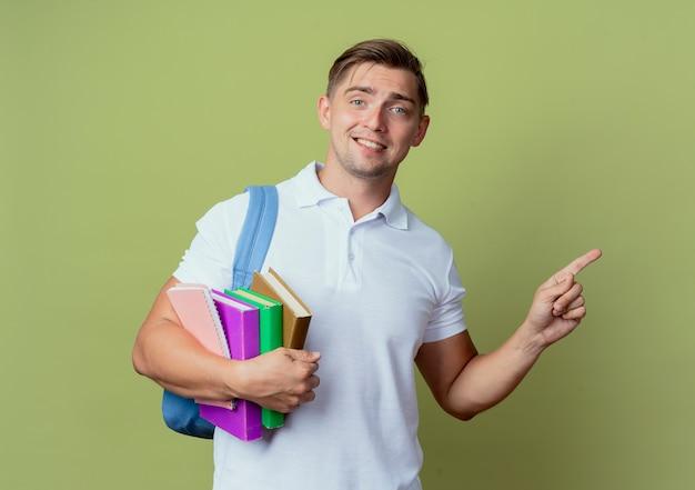 Jovem e bonito estudante sorridente usando uma bolsa com livros e pontos ao lado isolados em verde oliva com espaço de cópia