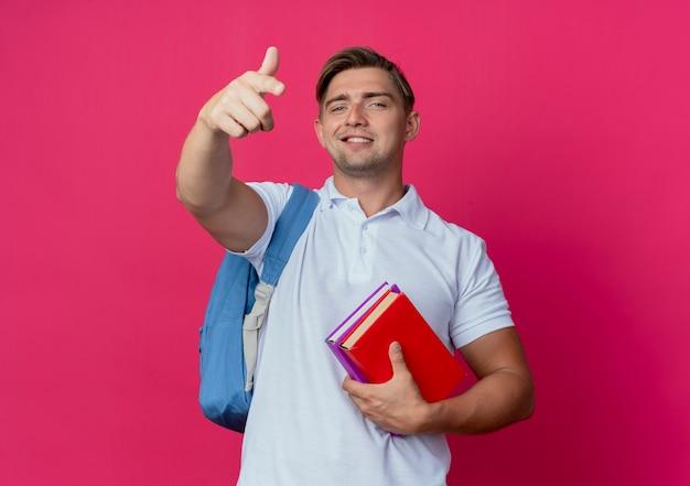 Jovem e bonito estudante sorridente usando uma bolsa com livros e pontos isolados na parede rosa