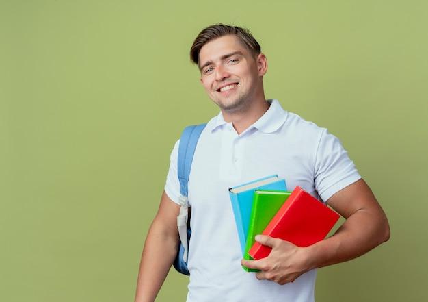 Jovem e bonito estudante sorridente usando uma bolsa com livros isolados em verde oliva
