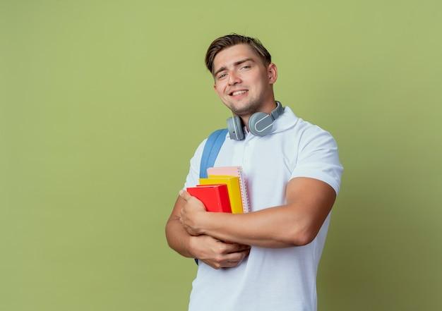 Jovem e bonito estudante sorridente usando uma bolsa com livros sobre verde oliva