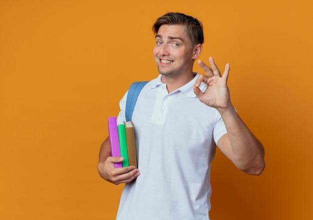 Jovem e bonito estudante sorridente usando uma bolsa com livros