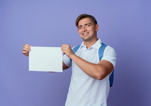 Jovem e bonito estudante sorridente usando uma bolsa de costas segurando um papel isolado no azul