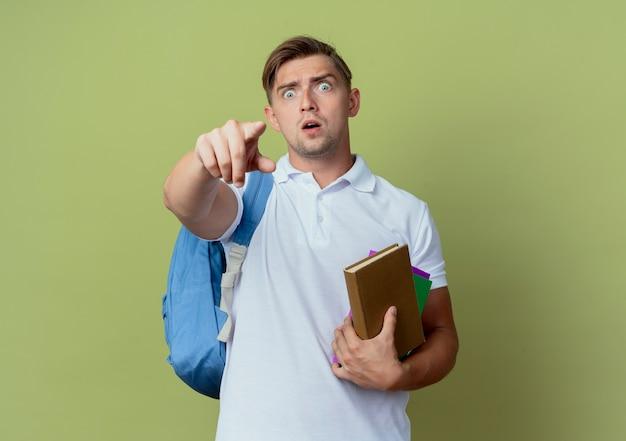 Jovem e bonito estudante surpreso com uma bolsa nas costas, segurando livros e apontando para a câmera