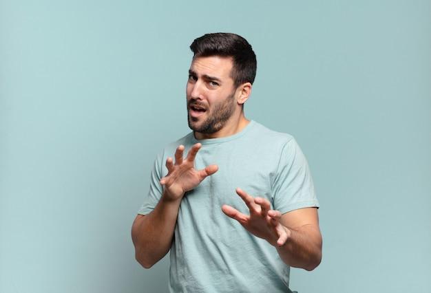 Jovem e bonito homem adulto sentindo-se enojado e com náuseas, se afastando de algo desagradável, fedorento ou fedorento, dizendo eca