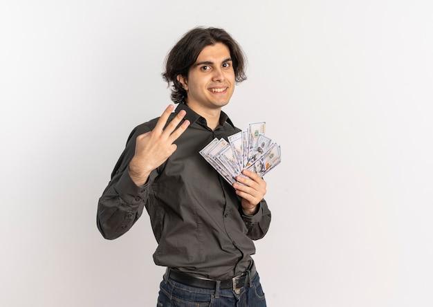 Jovem e bonito homem caucasiano sorridente segurando dinheiro e gesticulando três com os dedos isolados no fundo branco com espaço de cópia
