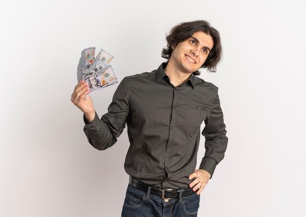 Jovem e bonito homem caucasiano sorridente segurando dinheiro e olhando para o lado isolado no fundo branco com espaço de cópia