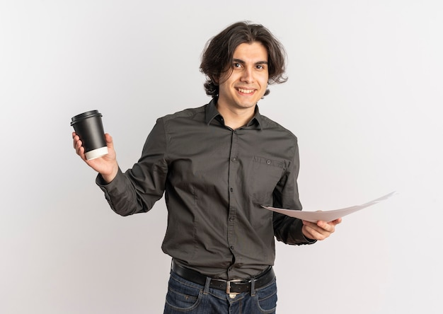 Jovem e bonito homem caucasiano sorridente segurando uma xícara de café e folhas de papel em branco isoladas no fundo branco com espaço de cópia