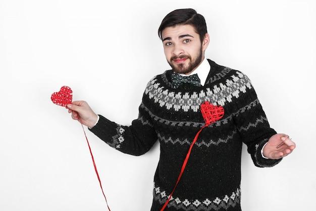 Jovem e bonito homem com barba em um suéter de malha com uma decoração em